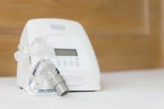Schlaf Apneatherapie, CPAP-Maschine mit Maske auf weißer Bettdecke Stockfoto