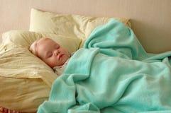 Schlaf des recht kleinen Mädchens auf großen Kissen. Lizenzfreies Stockfoto