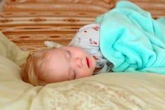 Schlaf des recht kleinen Mädchens auf großen Kissen. Stockfotos