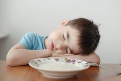 Schlafen über der Platte des Breis Stockfotografie