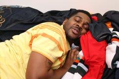 Schlafen auf Stapel von Kleidung Lizenzfreies Stockfoto