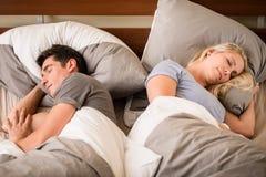 Schlafen des jungen Mannes und der Frau Rücken an Rücken Lizenzfreie Stockfotos