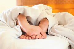 Schlafen kleines Kinderlustige schmutzige Füße auf weißer Bettwäsche Lizenzfreies Stockbild