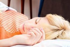 Schlafen mit der Hand auf Kissen Stockbild