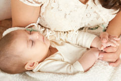 Schlafenbabyporträt in der Mutterhand, in der glücklichen Mutterschaft und im Kindheitskonzept Lizenzfreies Stockbild