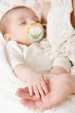 Schlafenbabyporträt in der Mutterhand, in der glücklichen Mutterschaft und im Kindheitskonzept, fokussieren an Hand Stockfotografie
