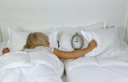Schlafende Dame Covering Alarm Clock Stockbilder