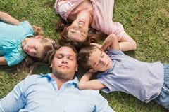 Schlafende Familie, die auf dem Gras in einem Kreis liegt Stockfoto