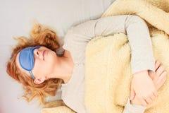 Schlafende Frau, die mit verbundenen Augen Schlafmaske trägt Lizenzfreies Stockbild
