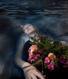 Schlafende Frau in einem dunklen Wasser von einem Fluss Stockbilder