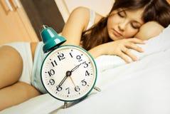 Schlafende Frau mit dem Wecker lizenzfreie stockfotografie