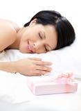 Schlafende Frau und Geschenk auf dem Bett Stockfoto