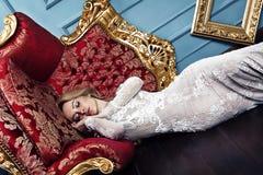 Schlafende schöne Blondine im Hochzeitskleid, Modekunstkonzept-Wundertraum Lizenzfreies Stockbild