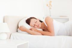 Schlafende schöne Frau, die auf einem Bett liegt Lizenzfreie Stockfotografie