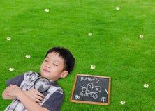 Schlafender Junge mit Lupe in der Rasenfläche Stockbilder