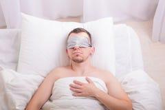 Schlafender junger Mann in der Schlafmaske auf Bett Lizenzfreies Stockbild