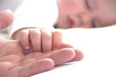Schlafender Kleinkindjunge hält die Hand des Vaters Lizenzfreies Stockfoto