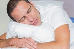 Schlafender Mann, der sein Kissen umarmt Stockfotografie