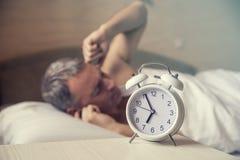 Schlafender Mann gestört bis zum frühem Morgen des Weckers Verärgerter Mann im Bett aufgewacht durch Geräusche Stockbild