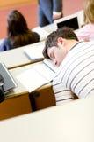 Schlafender männlicher Kursteilnehmer während einer Hochschullektion Lizenzfreie Stockbilder