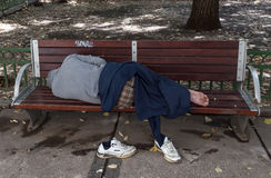 Schlafender obdachloser Mann auf der Bank Stockfotos