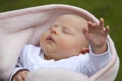 Schlafendes Baby, das heraus Hand erreicht Stockfoto