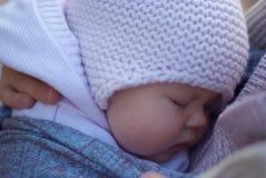 Schlafendes Baby in den Armen seiner Mutter Stockbild