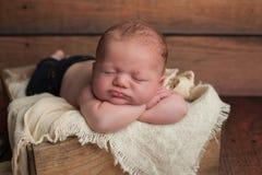 Schlafendes Baby in der hölzernen Kiste Stockbilder