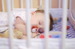 Schlafendes Baby mit Friedensstifter Stockfotos