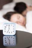 Schlafendes frühes des Weckers und der Paare morgens, vertikal lizenzfreies stockfoto