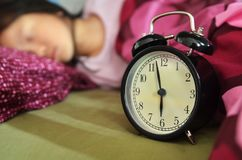 Schlafendes Kind im Bett und im Wecker Stockbilder