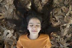 Schlafendes Mädchen in den Blättern Lizenzfreie Stockbilder