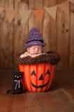 Schlafendes neugeborenes Baby, das ein Hexen-Kostüm trägt Lizenzfreies Stockfoto