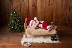 Schlafendes neugeborenes Baby, das Santa Suit mit Bart trägt Lizenzfreies Stockfoto
