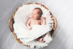 Schlafendes neugeborenes Baby in einer Verpackung auf weißer Decke lizenzfreies stockbild