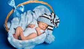 Schlafendes neugeborenes Baby, neugeborener Kinderschlaf im Korb, Studio-Portr?t auf Blau lizenzfreie stockfotos