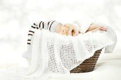 Schlafendes neugeborenes Schätzchen im Hut, der im Korb liegt Stockfotos