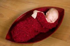 Schlafendes neugeborenes Schätzchen im roten Kokon Lizenzfreies Stockfoto