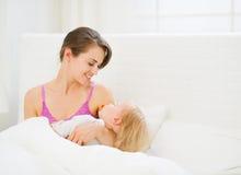 Schlafendes Schätzchen der glücklichen jungen Mutterholding Stockfoto