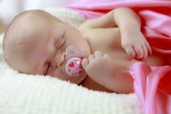 Schlafendes Schätzchen mit Friedensstifter Stockfoto
