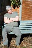 Schlafendes Sitzen des älteren Mannes auf Bank. Lizenzfreies Stockfoto