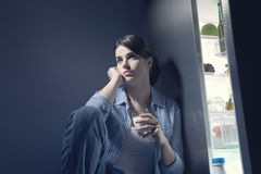 Schlaflose Frau, die ein Glas Milch isst stockfotografie