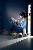 Schlaflose Frauenlesung in der Küche lizenzfreie stockfotos