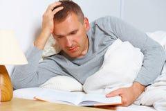 Schlafloser Mann, der ein Buch liest Stockfoto