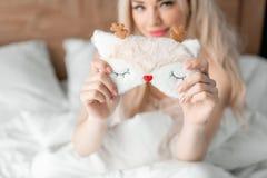 Schlafmaske im Vordergrund Junge Frau sitzt auf bequemem Bett und Griff in der Handmaske f?r das Schlafen Morgen im Hotel stockfotografie