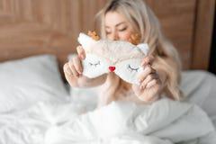 Schlafmaske im Vordergrund Junge Frau sitzt auf bequemem Bett und Griff in der Handmaske f?r das Schlafen Morgen im Hotel lizenzfreie stockbilder