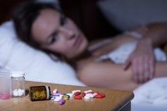 Schlaftabletten auf Nachttisch Lizenzfreie Stockfotos