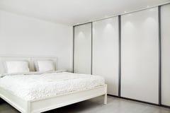 Schlafzimmer. Bett und ein Wandschrank. Lizenzfreie Stockfotografie