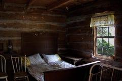 Schlafzimmer im antiken historischen Blockhaus Stockbilder