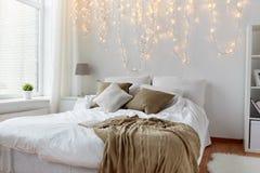 Schlafzimmer mit Bett und Weihnachtsgirlande zu Hause Stockbild